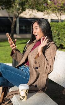 Junge asiatische frau mit langen schwarzen haaren, die hallo bei videoanruf mit handy auf einer bank sagt