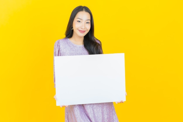 Junge asiatische frau mit leerer weißer reklametafel auf gelb