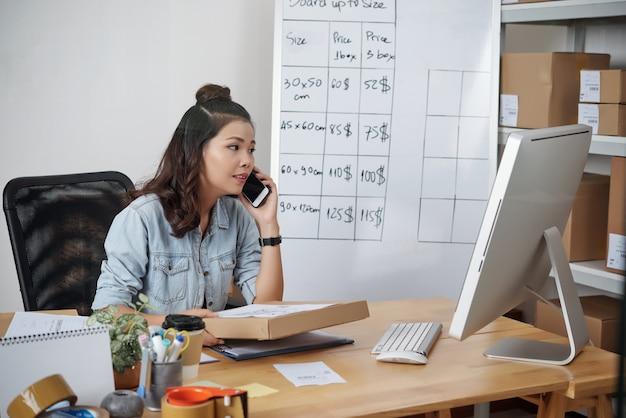 Junge asiatische frau mit lockigem haar, die mit computer am tisch sitzt und karton hält, während sie den paketempfänger anruft