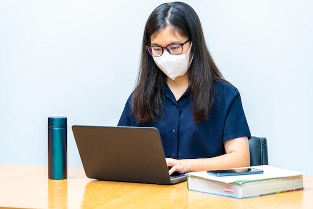 Junge asiatische frau mit n95-maske, die während der ausbreitung des covid-19-virus von zu hause aus an ihrem computer arbeitet