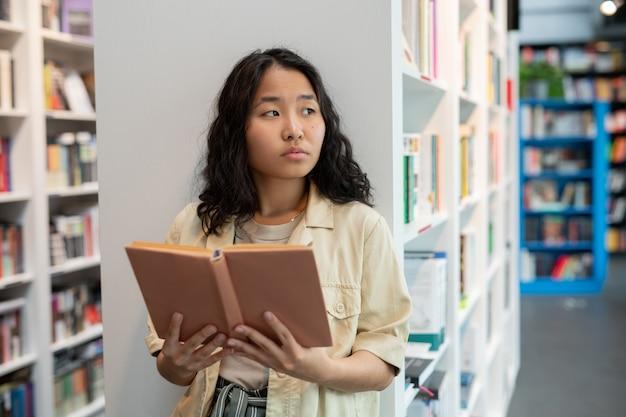 Junge asiatische frau mit offenem buch in der bibliothek