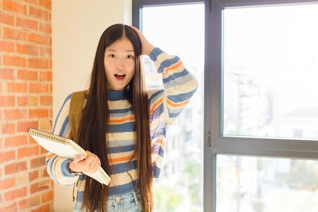 Junge asiatische frau mit offenem mund, die wegen eines schrecklichen fehlers entsetzt und schockiert aussieht und die hände zum kopf hebt