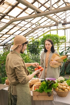 Junge asiatische frau mit papiertüte, die art von tomaten zum landwirt fragt, während sie es am bauernmarkt kauft