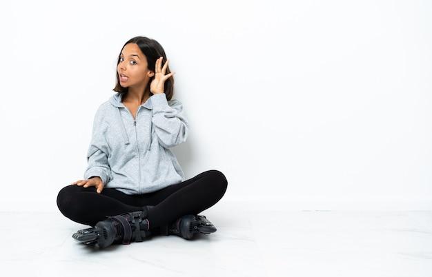Junge asiatische frau mit rollschuhen auf dem boden, der etwas hört, indem man hand auf das ohr legt