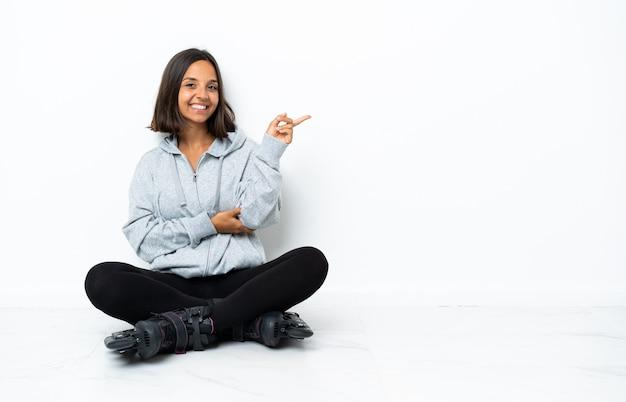 Junge asiatische frau mit rollschuhen auf dem boden, der finger zur seite zeigt