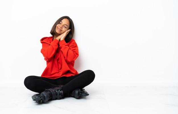 Junge asiatische frau mit rollschuhen auf dem boden, der schlafgeste im liebenswerten ausdruck macht