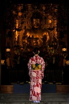 Junge asiatische frau mit rotem kimono japanisches traditionskleid stehender goldener buddha im tempel in japan anbeten