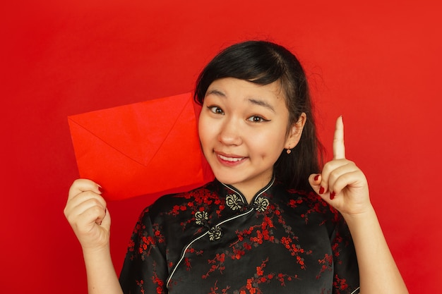 Junge asiatische frau mit rotem umschlag