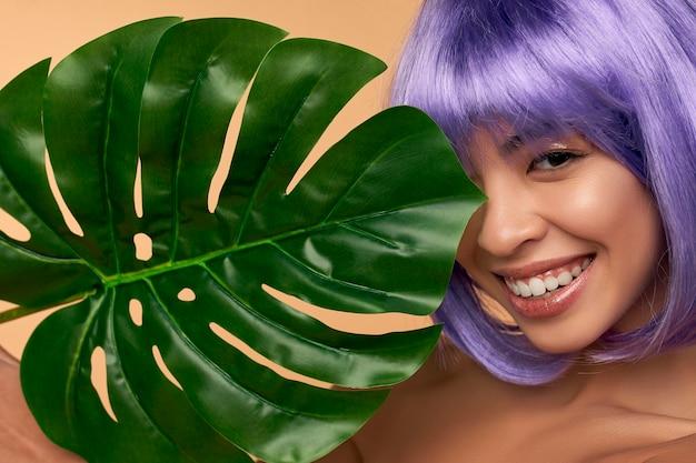 Junge asiatische frau mit sauberer strahlender haut in einer lila perücke und hellem haar mit einem grünen blatt auf beige