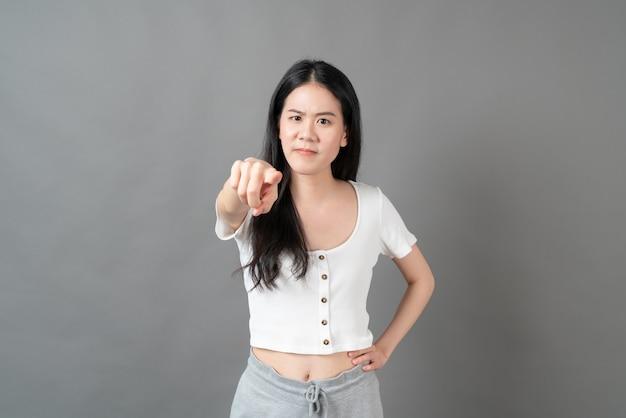 Junge asiatische frau mit schmollendem gesicht im weißen hemd auf grauem hintergrund
