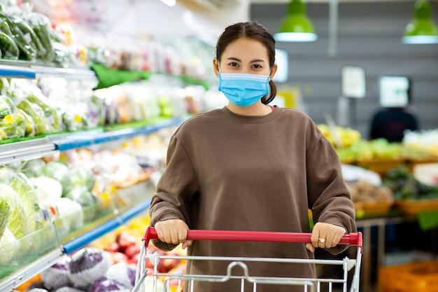 Junge asiatische frau mit schutzmaske, die einkaufswagen für den kauf von frischem gemüse im supermarkt während des virus-covid-19-ausbruchs drückt.