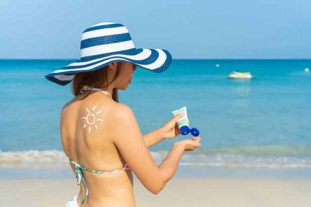 Junge asiatische frau mit sonnenform auf der schulter tragen sonnencreme auf ihre hand auf. sommer am strand konzept.