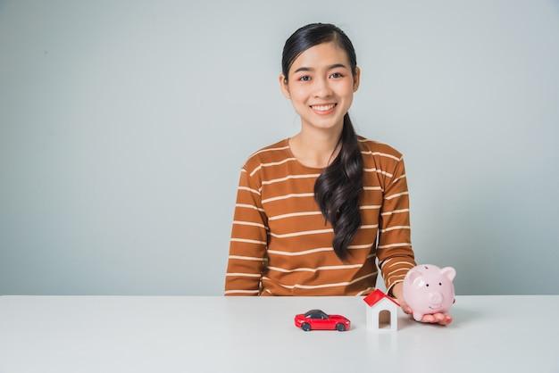Junge asiatische frau mit sparschwein und spielzeughaus und auto