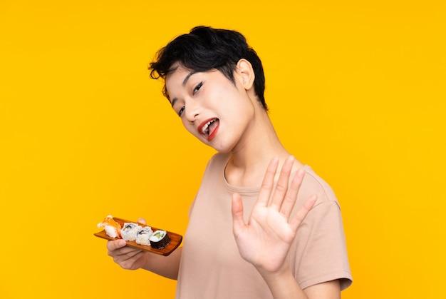 Junge asiatische frau mit sushi, das mit hand mit glücklichem ausdruck salutiert