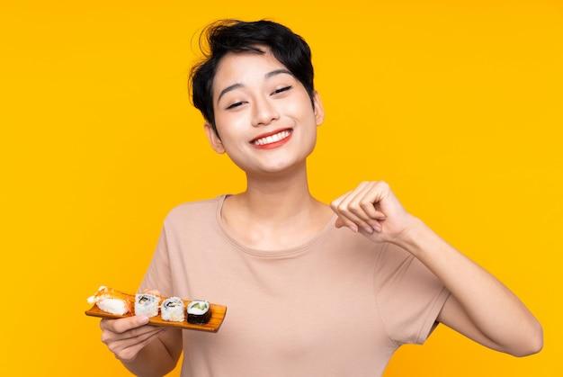 Junge asiatische frau mit sushi stolz und selbstzufrieden