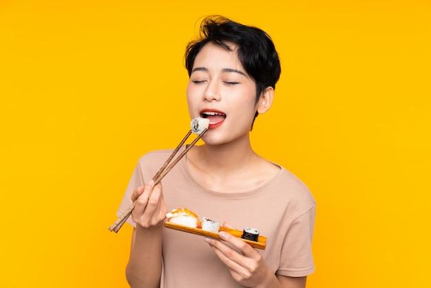Junge asiatische frau mit sushi über gelbem hintergrund