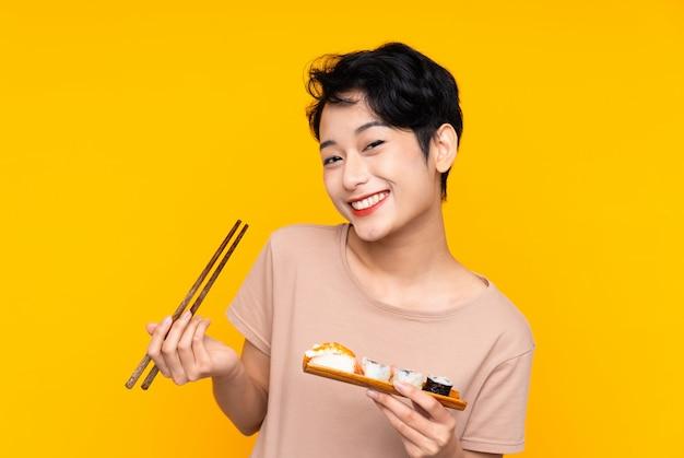 Junge asiatische frau mit sushi