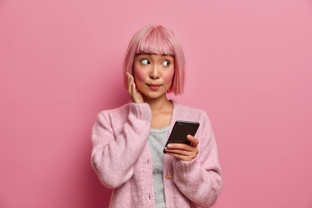 Junge asiatische frau mit überraschtem gesichtsausdruck schaut zur seite, in freizeitkleidung gekleidet, hält handy, surft in sozialen medien, sendet inhalte, teilt multimedia online,