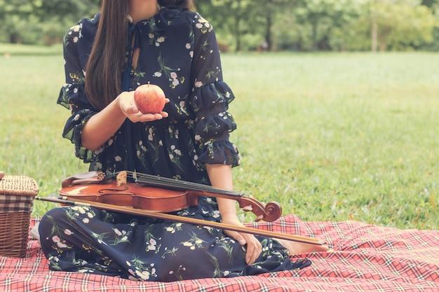 Junge asiatische frau mit violine und entspannung am garten.