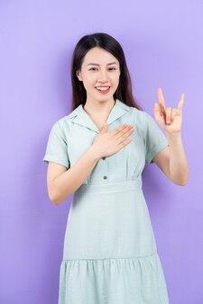 Junge asiatische frau posiert auf lila hintergrund
