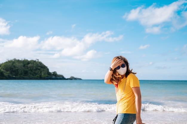 Junge asiatische frau reisen am strand in thailand, sommerkonzeptreise. frauen mit gesichtsmaske reisen am strand.