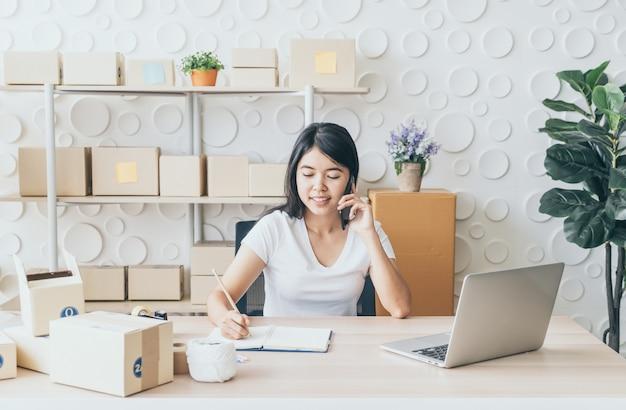 Junge asiatische frau starten kleinunternehmer, der mit digitalem tablet am arbeitsplatz arbeitet.
