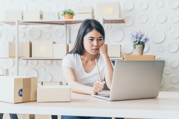 Junge asiatische frau starten kleinunternehmer mit digitalen tablet am arbeitsplatz arbeiten.
