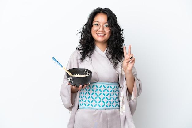 Junge asiatische frau trägt kimono isoliert auf weißem hintergrund lächelnd und zeigt victory-zeichen, während sie eine schüssel nudeln mit stäbchen hält