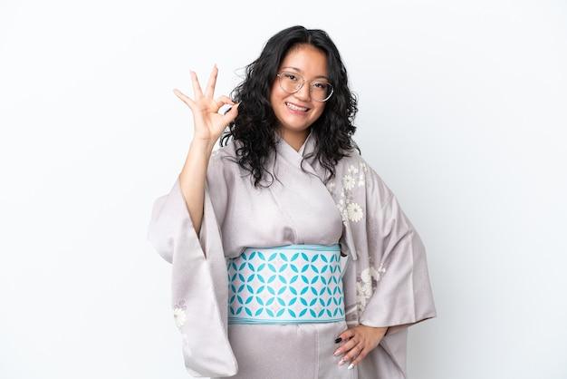 Junge asiatische frau trägt kimono isoliert auf weißem hintergrund zeigt ok zeichen mit den fingern