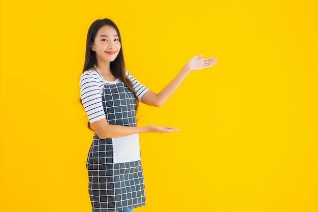 Junge asiatische frau tragen schürze mit lächeln glücklich