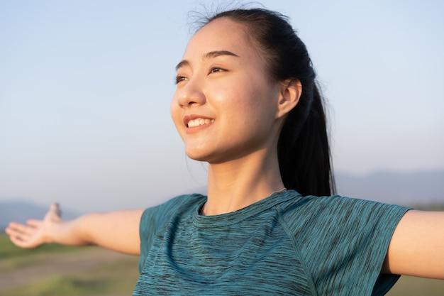 Junge asiatische frau trainiert mit yoga, während sie im sommer im freien steht