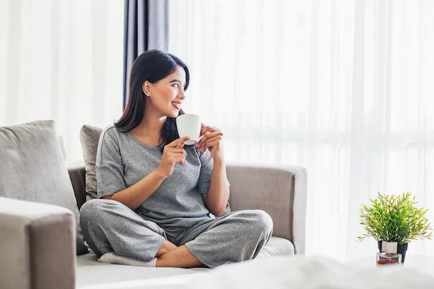 Junge asiatische frau trinkt kaffee auf einem schlafsofa zu hause