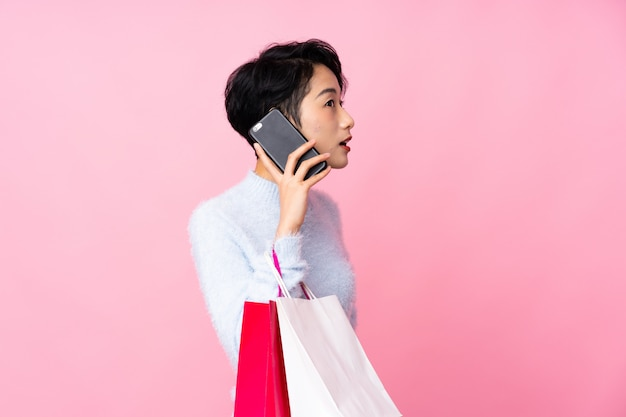 Junge asiatische frau über isolierte rosa wand, die einkaufstaschen hält und einen freund mit ihrem handy anruft