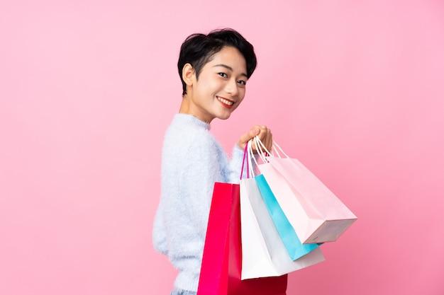Junge asiatische frau über isolierte rosa wand, die einkaufstaschen hält und lächelt