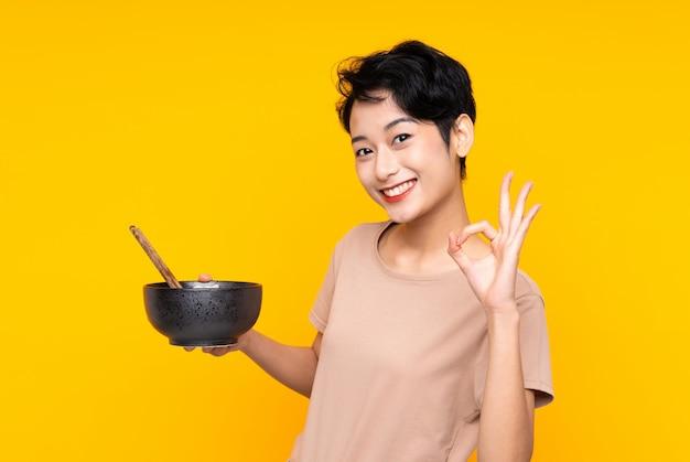 Junge asiatische frau über isolierter gelber wand, die ok zeichen mit den fingern zeigt, während eine schüssel nudeln mit stäbchen hält