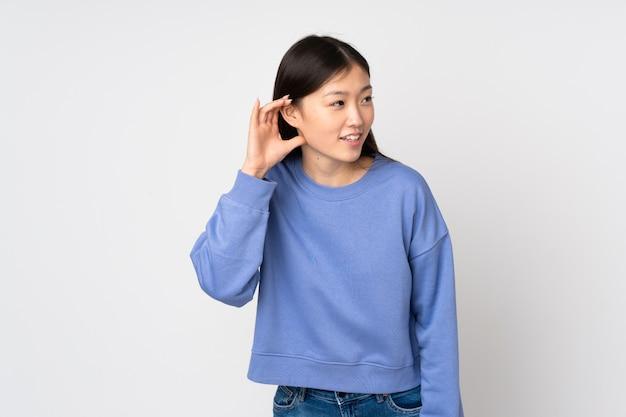 Junge asiatische frau über wand, die etwas hört, indem man hand auf das ohr legt
