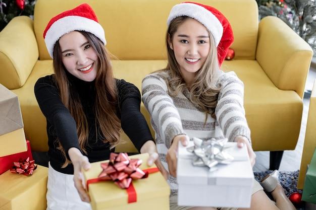 Junge asiatische frau und freundin, die geschenkboxen halten und mit glücklichem lächeln zu hause im weihnachtsfest zusammen schauen.