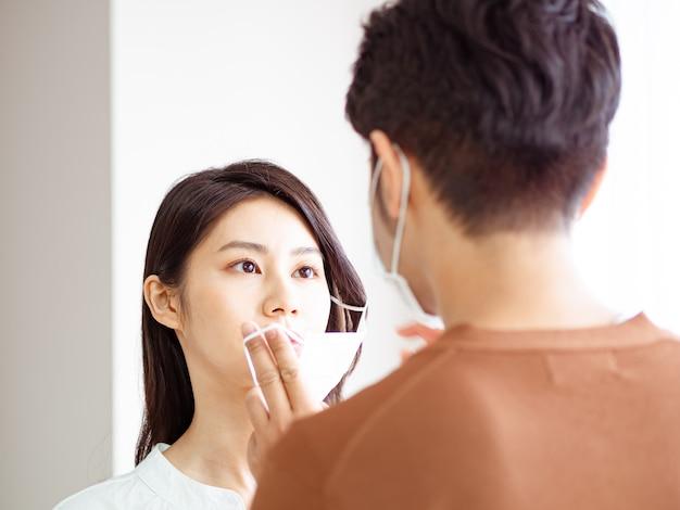 Junge asiatische frau und mann, die eine chirurgische maske tragen, um eine infektion in der häuslichen quarantäne zu verhindern