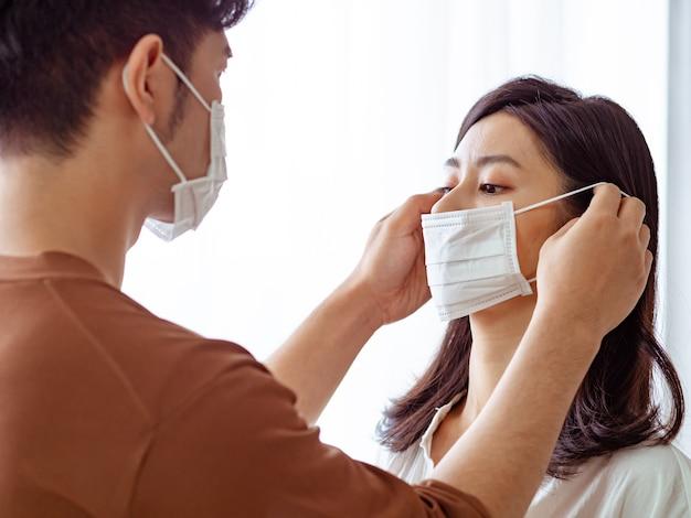 Junge asiatische frau und mann mit chirurgischer maske zu hause