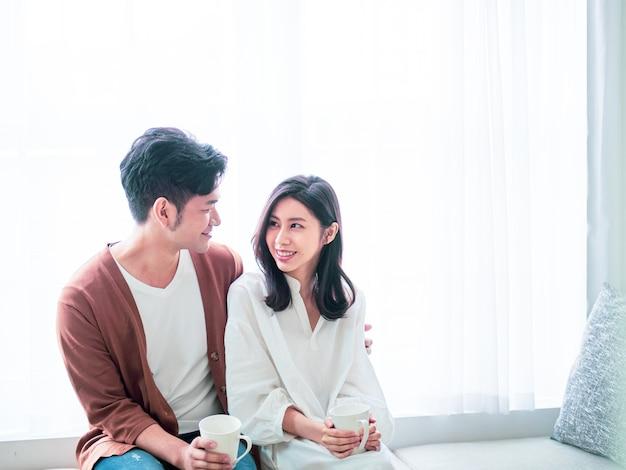 Junge asiatische frau und mann zu hause mit tasse kaffee in den händen.