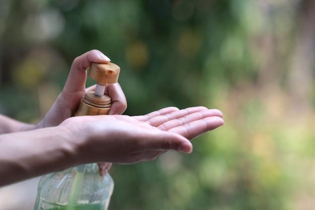 Junge asiatische frau unter verwendung der wäschehändedesinfektionsgelpumpenspender im freien natur