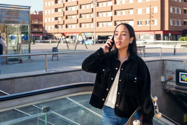 Junge asiatische frau verlässt die u-bahn-station mit einem skateboard in der hand, während sie telefoniert