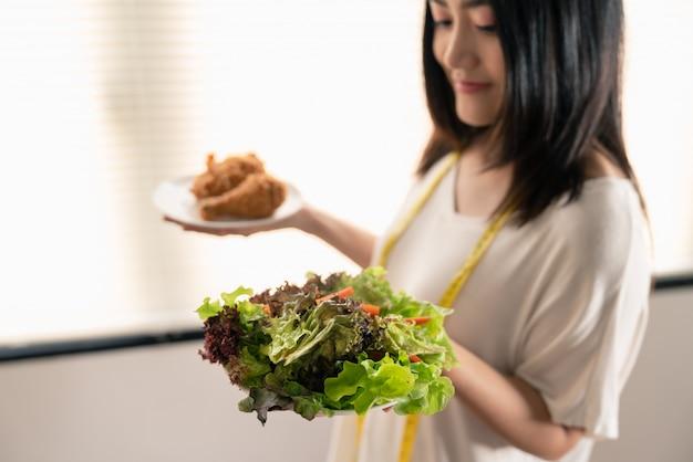 Junge asiatische frau verlieren das gewicht, das zwischen gemüsesalat und gebratenem huhn der ungesunden fertigkost in den tellern auf ihrer hand wählt