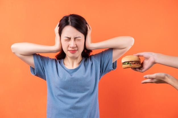 Junge asiatische frau versucht, die gewohnheit aufzugeben, hamburger zu essen