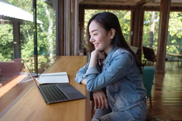 Junge asiatische frau videoanrufe mit ihrer freundin auf dem laptop im café online arbeiten