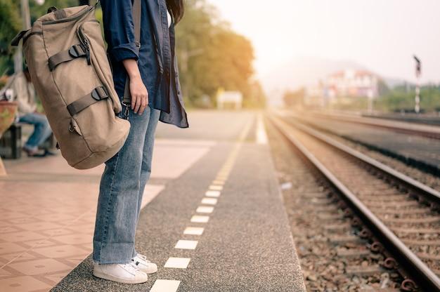 Junge asiatische frau wartet zug auf bahnsteig. konzept von tourismus, reisen und erholung.
