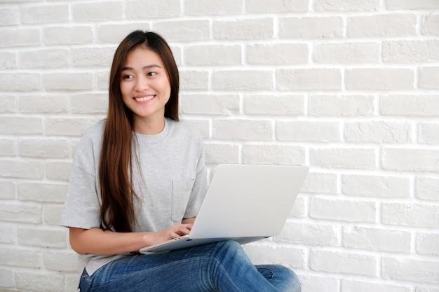 Junge asiatische frau, welche die laptop-computer sitzt vor weißem wandhintergrund mit spindel verwendet