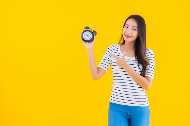 Junge asiatische frau zeigen uhr oder wecker