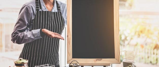 Junge asiatische frauen barista mit leerem tafelmenü im café