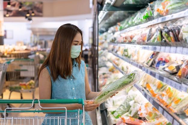 Junge asiatische frauen, die chirurgische maske tragen, die frisches gemüse im lebensmittelgeschäft am supermarkt kauft